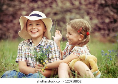 Little boy gives flowers to the little girl near the country house