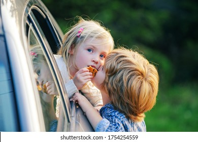 Little boy gives kiss for cute girl. Bye bye. Funny little couple saying goodbye before car travel. Farewell child concept