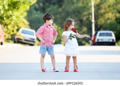 Little boy gives a red rose to girlfriend. Little girl in her mother's red shoes and a little boy in red sneakers on the street