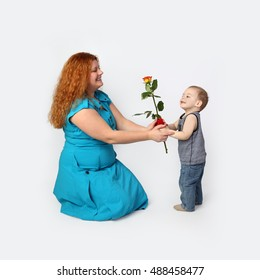 Little boy gives rose to his happy mother - Redhead woman with child on gray background in square