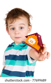 The little boy gives the toy house