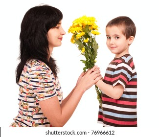 Little boy gives yellow flowers to his mom isolated on white