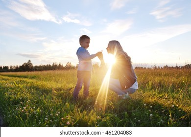 Little boy giving flower to his mom on field in evening sunlight