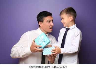 Little boy giving present to his father on color background