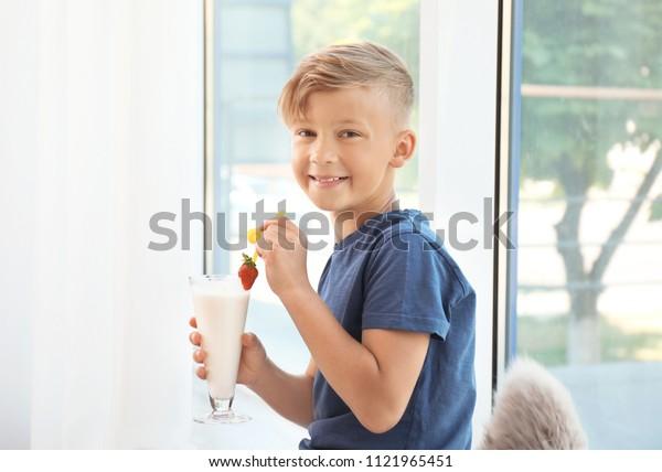 Little boy with glass of milk shake near window indoors