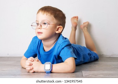 A little boy in glasses and in a blue t-shirt with a blue smart watch on his hand is lying on the floor on a white background.