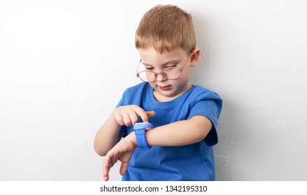 A little boy with glasses and a blue T-shirt looks at his smart watch against the background of a white wall.