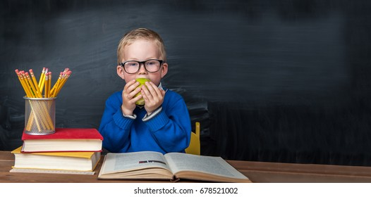 Little boy in glasses at desk in front of chalkboard eating apple. Schoolboy having an apple during his lunch break. healthy food for kids. Back to school