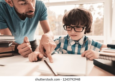Little Boy in Glasses Doing Homework with Father. Education at Home. White Table in Room. Sitting Boy. Young Father. Lesson at Home. Education Concept. Writing in Notebook. Boy in Shirt.