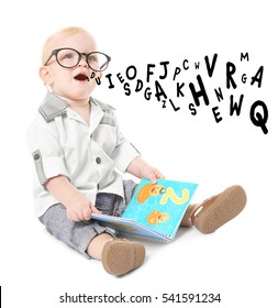 Little boy in glasses with first book and alphabet letters on white background. Speech therapy concept
