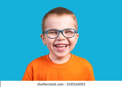 The little boy in glasses laughs. Isolated on a blue background.