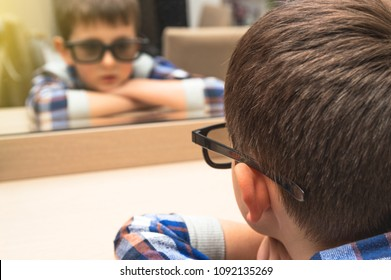 Little boy with glasses looks at himself in the mirror