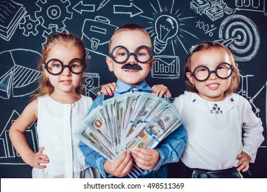 Little boy in glasses and mustache on dark background with a pattern. He holds banknotes in hand. Two girls standing the sides