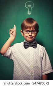 "Little boy with glasses standing in front of chalkboard with bulb drawing on it and he is making ""I have an idea"" gesture"
