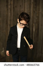 Little boy in glasses and suit, standing. Over dark background.