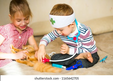 little boy in the glasses with syndrome dawn and blonde girl play with toys and ginger cat