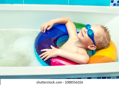 A little boy  in goggles is floating in an inflatable circle in the bathroom. Dreams about summer.