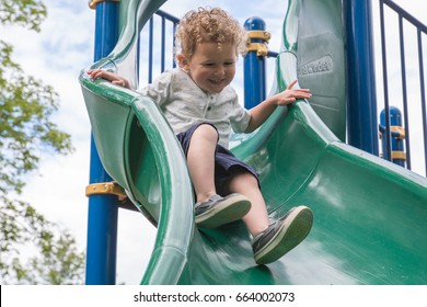 Little boy is going down a slide at the playground. He is laughing and having fun on the jungle gym at the park. He is in preschool. Back to school, recess, summer vacation