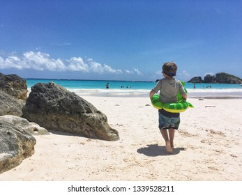 Little boy going for a swim in the turquoise tropical water with his floaty frog ring