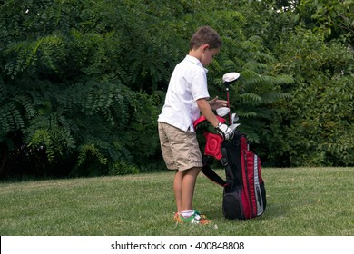 Little boy golfer with his golf bag on the fairway prepares for next shot