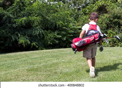 Little boy golfer walking with his golf bag on the fairway