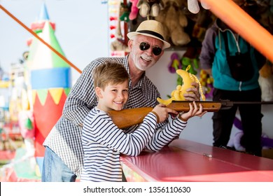 Little boy with grandfather having fun at amusement park