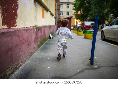 the little boy in the gray jacket and pants happily runs along an asphalt path separate from the parents, a simple children's happiness from a walk on a summer day