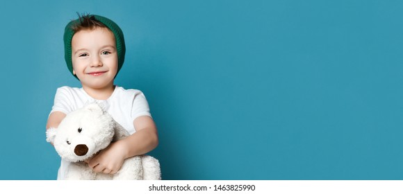 Little boy in green hat hold polar bear toy smiling. International day of polar bear concept on blue background