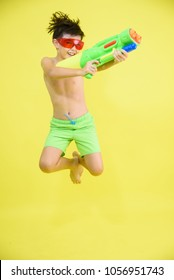 little boy with green short playing water gun Songkran festival yellow background