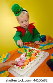 little boy in a green suit sitting at a table eating cake
