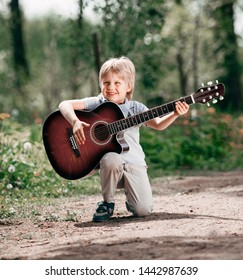 little boy with guitar on the Boulevard in the Park