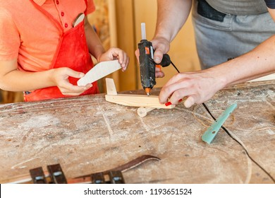 little boy hand works creating wooden airplane toy in the carpentry. Woodwork classes for children and creativity concept