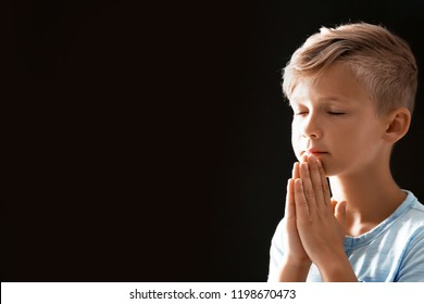 Little boy with hands clasped together for prayer on black background. Space for text