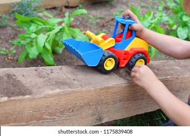 Little boy hands playing with colorful toy car bulldozer and soil in garden outdoors in summer day. Children outdoor activities and childhood concept.