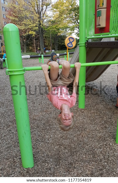 Little boy hanging upside down on a bar at a bright green playground.
