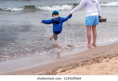 A little boy happily kicks the water as he and his mom stroll along the shores of Lake Michigan USA