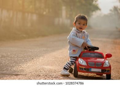 Little boy is a happy driving big toy car ,Child enjoying warm summer day in sunrise morning