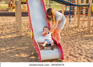 The little boy happy outdoors in playground with his parents