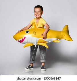 little boy has a balloon in the shape of a yellow shark fish, celebrates a holiday, has a wide smile, stands on a light background, being in a good mood. Children and holiday concept