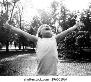 Little boy has fun in the summer rain, black and white