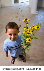 A little boy has gone into the garden and picked some flowers, tracking mud into the house behind him.