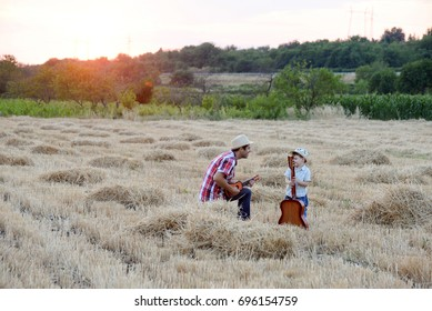 Little boy with hat and his father playing guitar at hay bale at sunset. Portrait of child and father