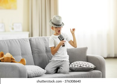 Little boy in a hat singing into the microphone on a sofa at home