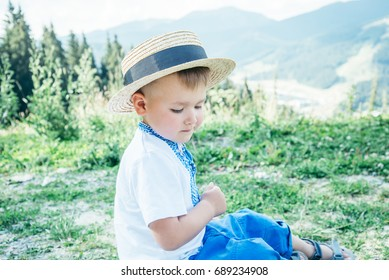 little boy in hat sitting on the ground on the top of the mountains