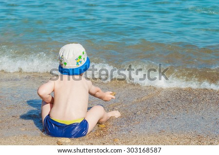 Little Boy In The Hat And A Speedo Throws A Stone Into The Blue Sea