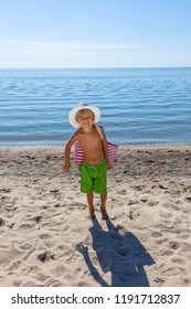 Little boy in hat standing on the beach. Child on summer holidays with beautiful sea, sand and blue sky. Happy kid on vacation in sunny day.