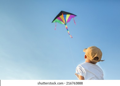 Little boy have fun playing with kite outdoors, focus on boy