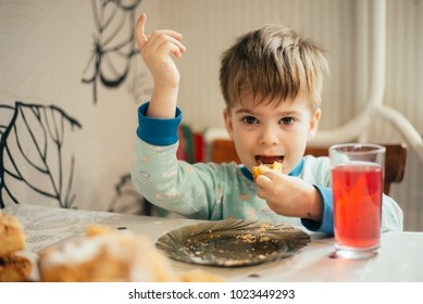 Little boy having breakfast in the kitchen. The boy is eating a croissant. Breakfast table with boy. Child have a breakfast