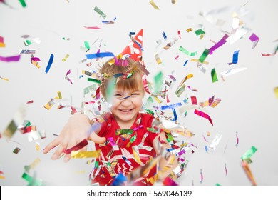 Little boy having fun celebrating birthday. Portrait of a child throws up multi-colored tinsel and confetti. Positive emotions.