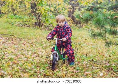little boy having fun on bikes in autumn forest. Selective focus on boy.